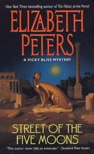 The cover of Street of the Five Moons depicts a slender statue of a cat.