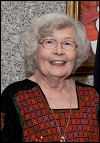 A photo of Barbara Mertz, white woman with white hair, smiling, wearing glasses and a square-collared patterned shirt.